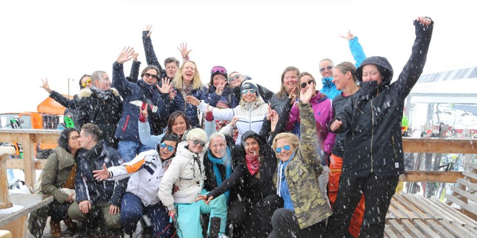 Group of lesbians smiling and celebrating in Davos with a snowing background