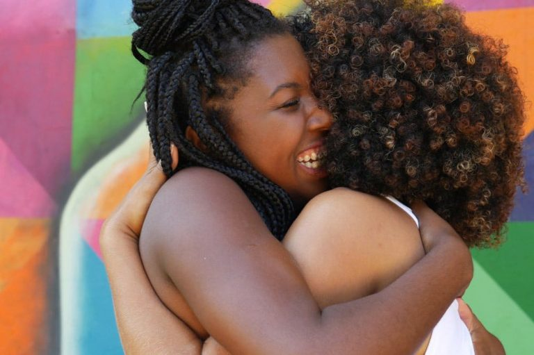 Two black women huging and smiling