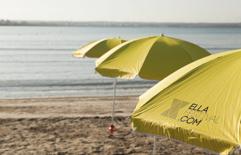 Tres sombrillas amarillas en la playa con el mar de fondo