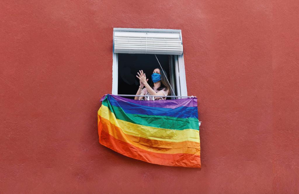 una mujer lesbiana tiene una bandera LGBT en la ventana de su casa