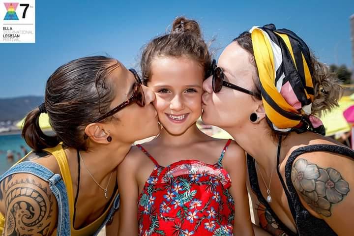 Dos mujeres lesbiana con su hija en la playa
